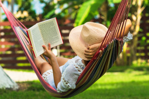 Travel Planning Deals woman reading in a hammock